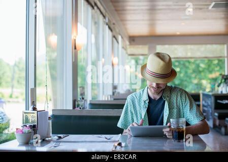 Un homme portant un chapeau assis dans une salle à manger à l'aide d'une tablette numérique. Banque D'Images