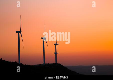 Silhouette éoliennes sur la montagne au coucher du soleil Banque D'Images