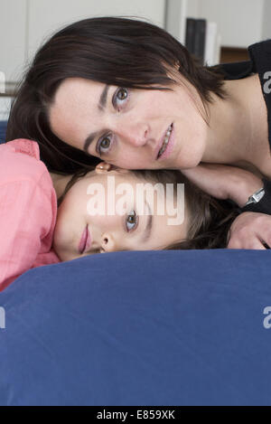 Mère et fille lying together on bed, portrait Banque D'Images