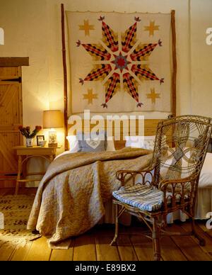 Patchwork tenture murale au-dessus de lit avec couette en pays cvream avec canne ouvragée+chaise en bambou Banque D'Images