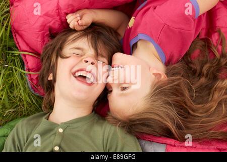 Garçon et fille riant tout en jetant sur les sacs de couchage Banque D'Images