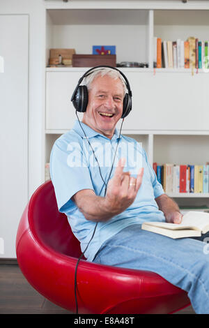 Senior man sitting in armchair listening to music Banque D'Images