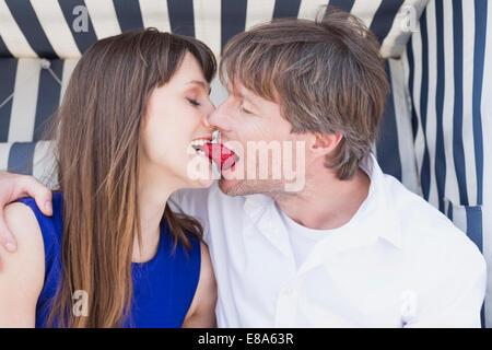 La fraise au couple en osier couvert chaise de plage, smiling Banque D'Images