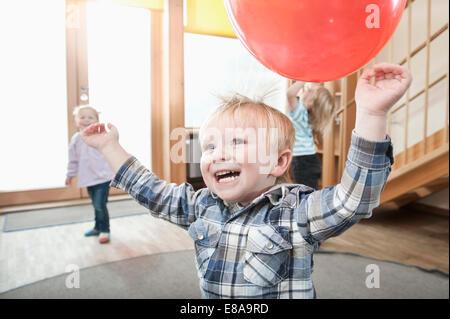 Les enfants jouent avec des ballons rouges en maternelle Banque D'Images