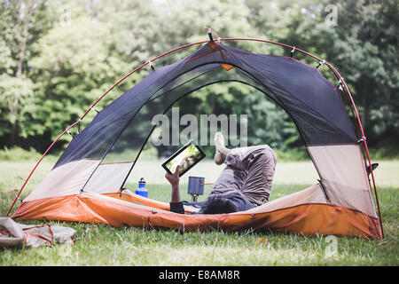 Young man lying in tent using digital tablet Banque D'Images