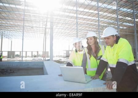 Les gestionnaires du site et l'architecte looking at laptop on construction site Banque D'Images
