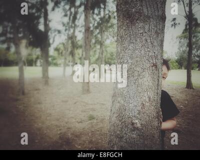 Boy Hiding behind a tree Banque D'Images