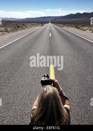 Woman taking photograph of empty road, en Californie, l'Amérique, USA Banque D'Images