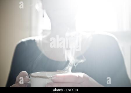 USA, Wyoming, vue de femme à boire du thé chaud ou de café en café Banque D'Images