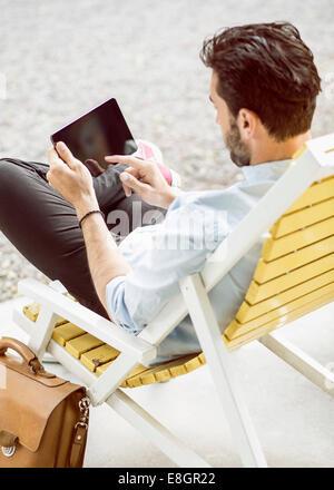 Vue arrière du businessman using digital tablet on lounge chair at park Banque D'Images