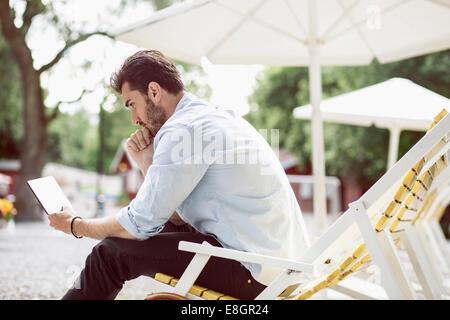 Vue latérale du businessman using digital tablet on lounge chair at park Banque D'Images