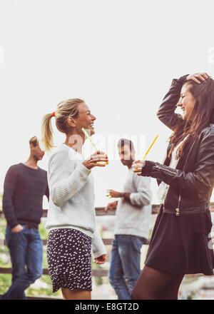 Happy female friends avec boissons sureau bénéficiant d at rooftop party Banque D'Images