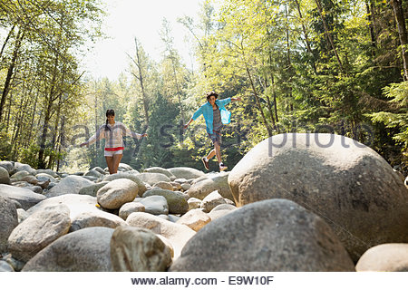 Friends walking on rocks in woods Banque D'Images