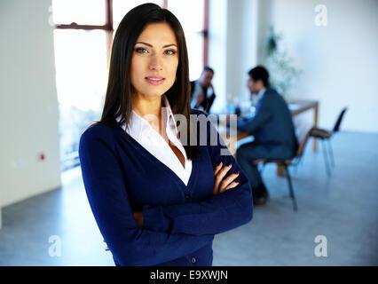 Belle femme debout les bras croisés avec des collègues à l'arrière-plan Banque D'Images