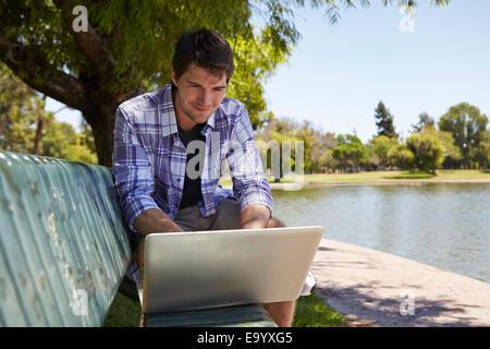 Man using laptop on park bench Banque D'Images