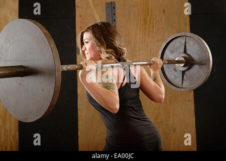 Jeune femme barbell levage in gym Banque D'Images