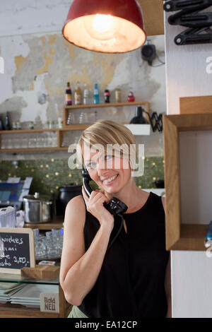 Mid adult woman on phone cafe Banque D'Images