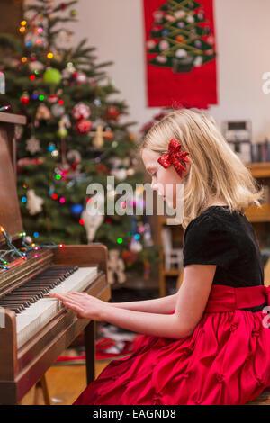Fillette de six ans portant une tenue habillée, arc rouge dans ses cheveux, jouer du piano, Arbre de Noël dans l'arrière Banque D'Images