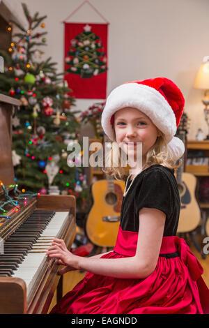 Une fillette de six ans portant une robe et un chapeau de Père Noël, jouer du piano, Arbre de Noël dans l'arrière Banque D'Images