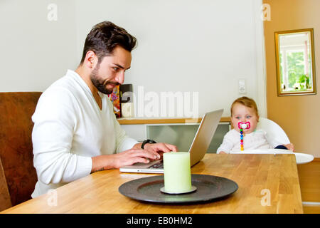 Père travaillant à domicile, baby-sitting sur une chaise haute Banque D'Images