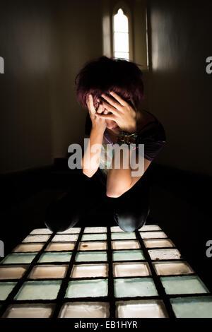 Une jeune femme désespérée adolescente dans une cellule de prison de prison type location avec la lumière pénétrant Banque D'Images