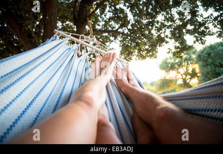 Couple relaxing in hammock under tree Banque D'Images