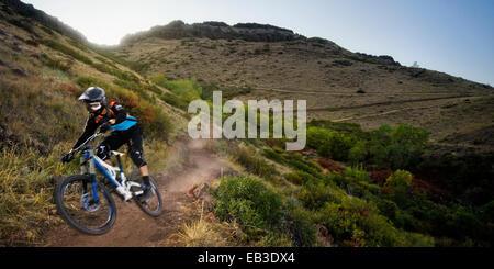 USA, Californie, Comté de Jefferson, Golden, promenades en vélo de montagne vers le bas laissant nuage de poussière Banque D'Images
