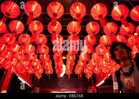 Homme debout en dessous des lampions rouges au temple de Jin Yuan, Jakarta, lors de la célébration du Nouvel An Banque D'Images