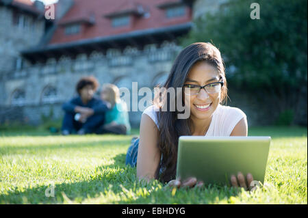 Young woman lying on grass using digital tablet Banque D'Images