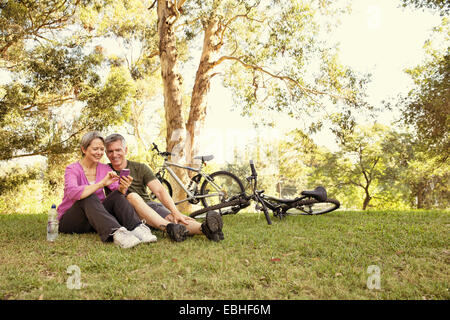 Vélo mature couple sitting in park looking at smartphone Banque D'Images