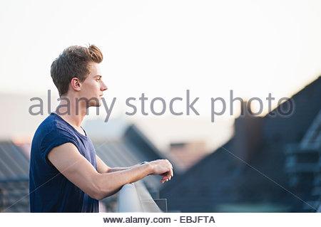 Jeune homme sur le toit, looking at view Banque D'Images