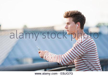 Jeune homme sur le toit, le port d'écouteurs et le holding smartphone Banque D'Images