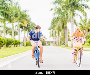 USA, Floride, Jupiter, jeune couple roulant vélos le long de rue avec palmiers Banque D'Images
