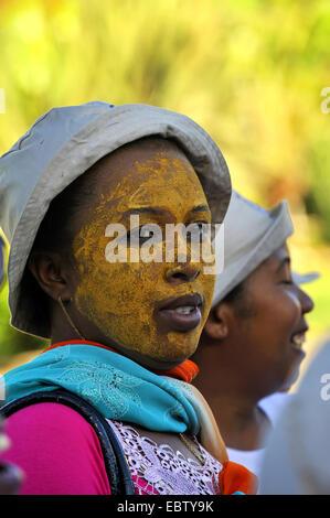 Femme à la peau sombre visage peint en jaune, Madagascar Banque D'Images