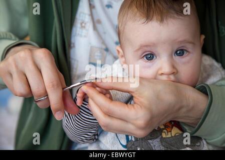 Bébé reçoit tape nails Banque D'Images