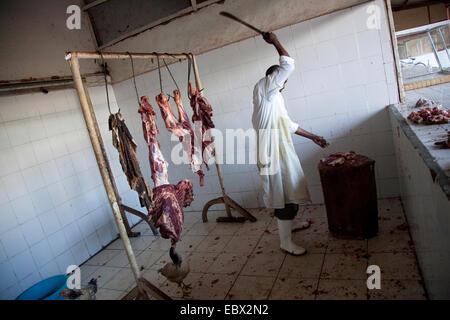 Couper la viande de boucherie sur un rondin de bois, le Rwanda, Kigali, Nyamirambo Banque D'Images