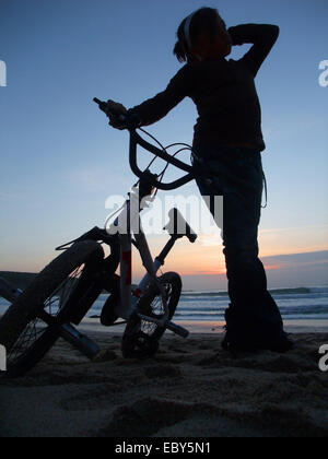 Close up of silhouette de jeune fille debout près de son vélo BMX sur le sable près de l'eau au coucher du soleil Banque D'Images