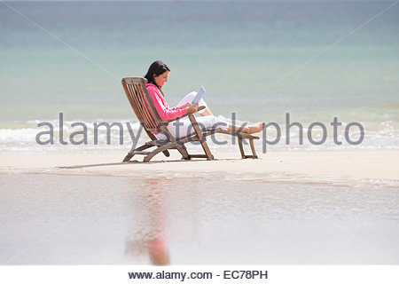 Woman using digital tablet in deck chair on beach Banque D'Images