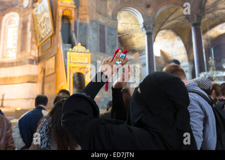 Femme musulmane à Sainte-Sophie, le Musée Ayasofya mosquée Muzesi portant le niqab en utilisant smartphone pour Banque D'Images