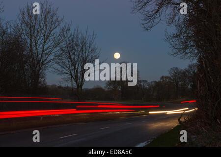 Une voiture sur une route de campagne avec une pleine lune près de Preston, Lancashire, Royaume-Uni. Banque D'Images