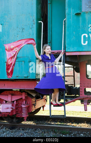 Woman waving avec foulard sur wagon train escaliers Banque D'Images