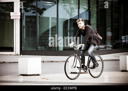 Young Woman riding bicycle on city street Banque D'Images