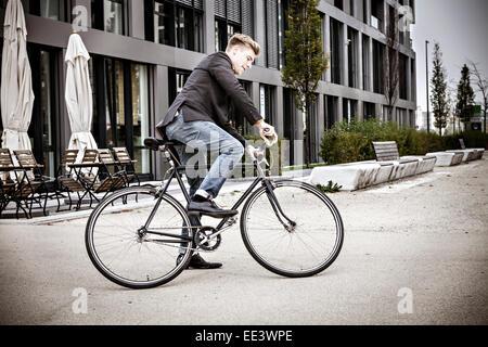 Young Woman riding bicycle on city street, Munich, Bavière, Allemagne Banque D'Images