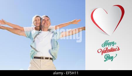 Image composite de happy senior man giving his partner un piggy back Banque D'Images