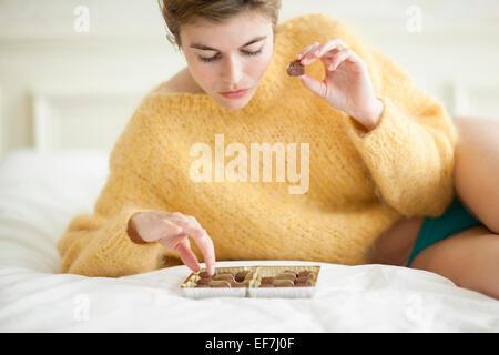 Femme mangeant du chocolat sur lit Banque D'Images