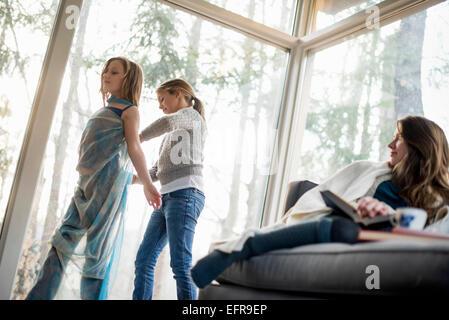 Deux filles debout dans un salon, dressing up, une femme assise sur un canapé, à regarder. Banque D'Images