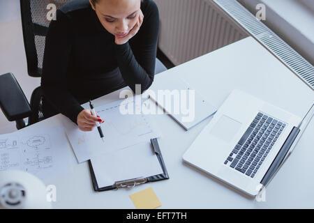 Vue de dessus de l'analyse de la croissance de l'entreprise femme sur une carte alors qu'il était assis à son bureau Banque D'Images