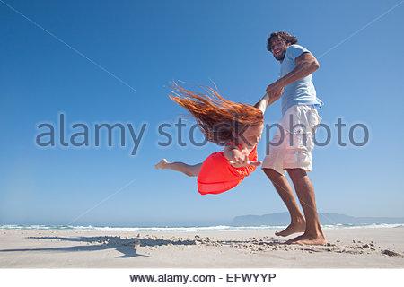 Smiling Father swinging fille jouant autour sur sunny beach Banque D'Images