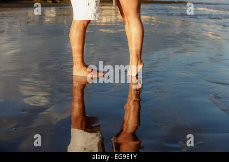 La section basse de jeune couple standing on beach Banque D'Images