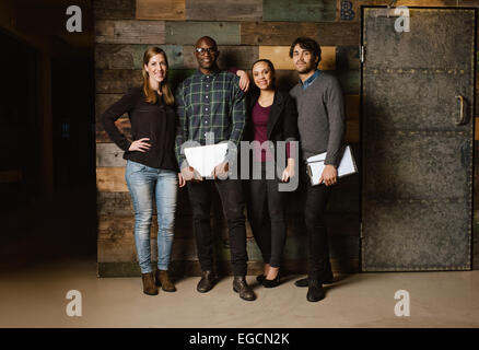 Portrait de réussite business team standing ensemble contre la paroi en bois. Longueur totale de droit d'un groupe Banque D'Images